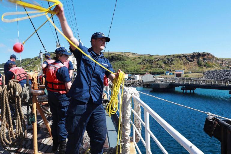O marinheiro David Demo, lança a retenida para o pessoal em terra, no cais militar da Praia da Vitória. (foto US Navy Ruben Reed)