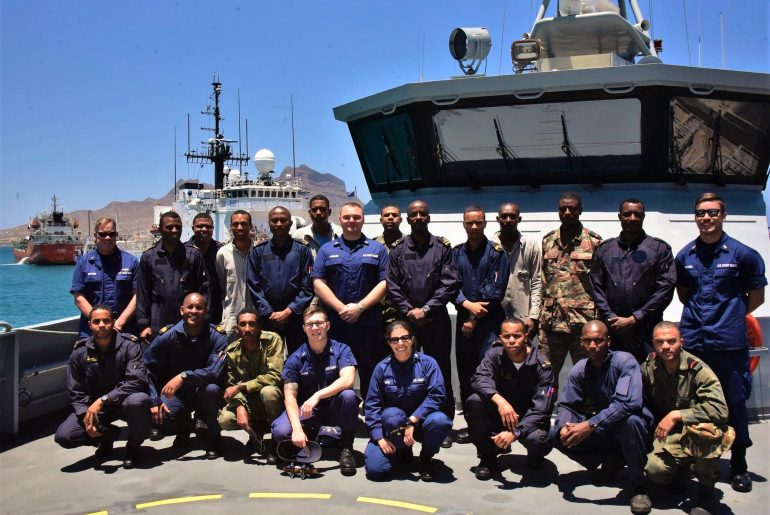 Crew members assigned to USCG cutter Thetis (background) pose with members of the Cabo Verdean Coast Guard and Maritime Police following a successful Operation Junction Rain (OJR) Phase I, May 2, 2019. OJR is a part of the Africa Maritime Law Enforcement Partnership, a U.S. Naval Forces Europe-Africa/U.S. 6th Fleet-facilitated initiative that aims to enhance the maritime enforcement capabilities of African partners in order to improve management and security of the maritime domain. (photo by courtesy)