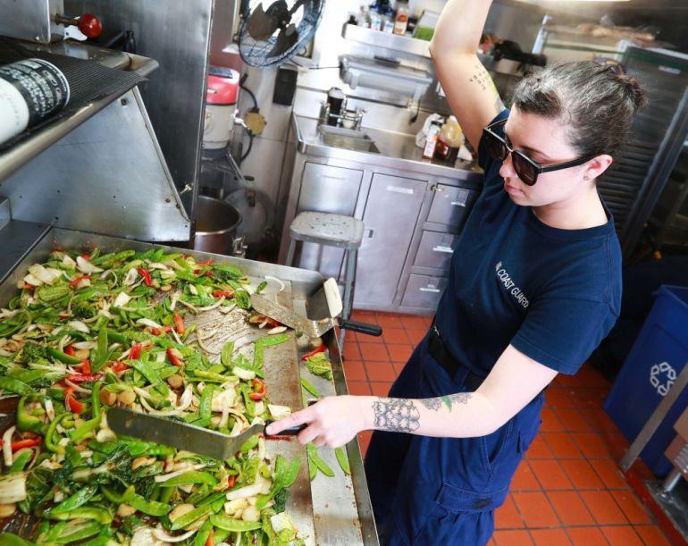 A marinheira cozinheira Kellie Lundy, a saltear vegetais na cozinha de bordo (foto US Navy Ruben Reed).