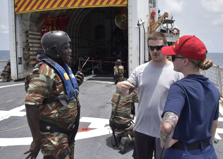 A Benin Coast Guard boarding officer aboard the USCGC THETIS talks with a law enforcement instructor, for a mock fisheries boarding during Obangame Express 2019 training exercise, on March 15, while transiting along the West African Coast in the Gulf of Guinea. (USNavy photo by Jonathan Lally)