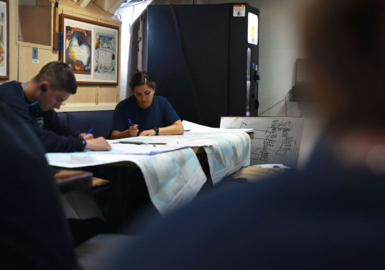 os marinheiros Sean Tocci e Valeree Sanchez, a marcarem linhas de resguardo nas cartas de navegação (foto US Navy Ruben Reed)