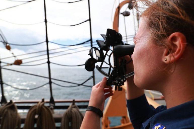 A Cadete Audrey Bartz, da USCG Academy, treina a utilização do sextante em navegação oceânica (foto US Navy Ruben Reed)