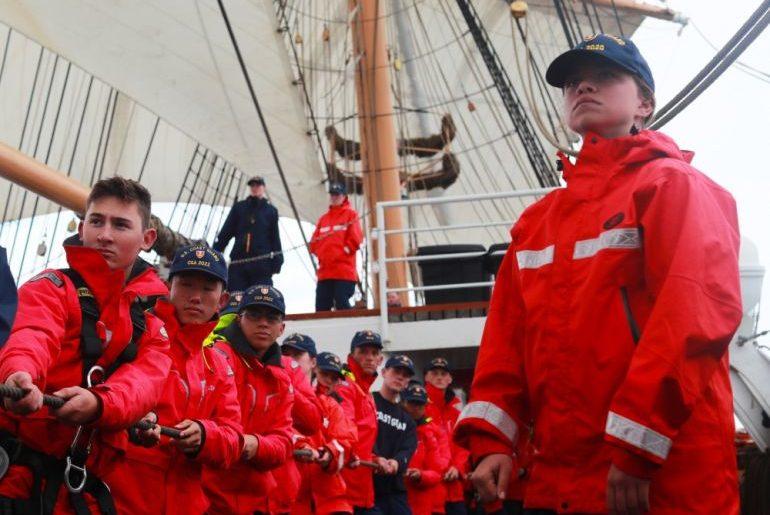 Cadetes em postos de faina de velas, a colher uma escota, ajudando a manobra do navio (foto US Navy Ruben Reed)