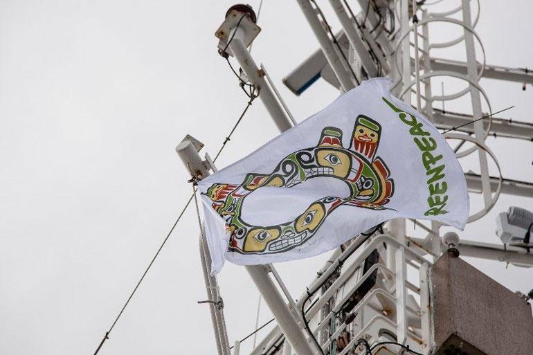 Uma bandeira, com o logo GREENPEACE e o símbolo SISIUTL, drapeja içada numa adriça do navio ESPERANZA (foto Joseph Strohan, Greenpeace)