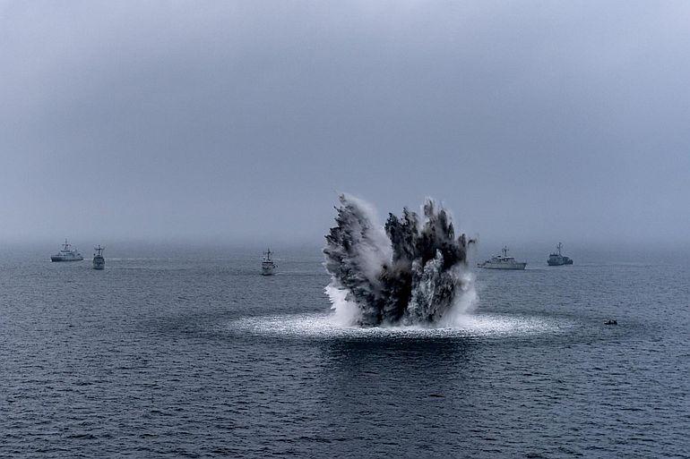 Explosão duma mina pela força Standing NATO Minecountermeasures Group One (SNMCMG1). A NATO é a mais antiga e bem-sucedida aliança militar da história comtemporânea.
