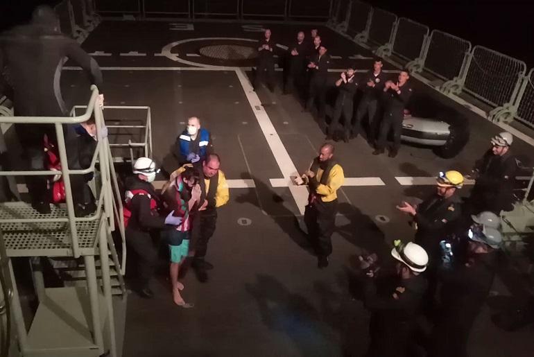 O náufrago, acompanhado pelo enfermeiro do NRP SETÚBAL é recebido com uma enorme ovação da guarnição do navio português (imagem Marinha Portuguesa)