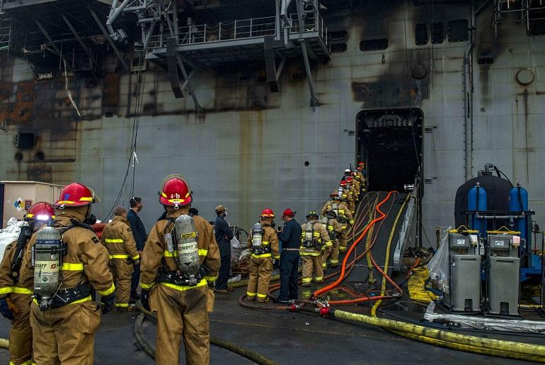 Pessoal fresco entra a bordo para render os camaradas que combatem o incêndio a bordo do navio doca norte-americano. (imagem US Navy)