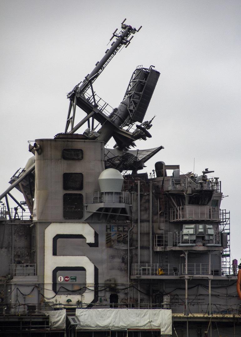 O mastro de vante, contendo os sensores mais importantes do navio, jaz tombado sobre a cobertura calcinada da ponte do USS BONHOMME RICHARD (imagem US Navy)
