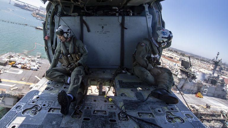 Tripulantes dum helicóptero naval SH-60 Seahawk, empregue no combate ao incendio observam o estado de destruição das superestruturas e do convés de voo do USS BONHOMME RICHARD LHD-6 (imagem US Navy)
