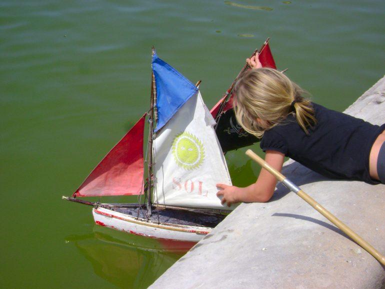 Uma criança lança à água um modelo de barco à vela.