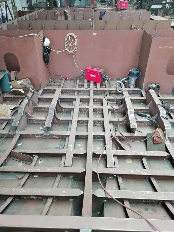 Fase inicial de construção do casco com montagem de perfis soldados. A imagem mostra a casa da máquina onde são visíveis os apoios dos motores.