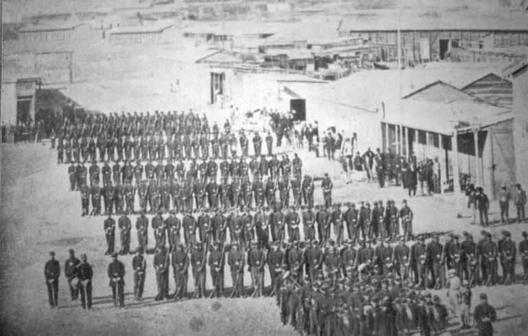 Soldados do batalhão nº3 de Linha do Exército do Chile, formados na Plaza Colón, Antofagasta, durante la Guerra del Pacífico (1879) (Álbum gráfico militar de Chile, Campaña del Pacífico)
