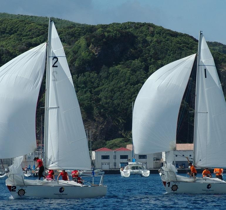 Dois J24, em regata, passam frente ao Monte da Guia, na ilha do Faial, durante o Campeonato Regional nos Açores 2008 (imagem A. Peters)