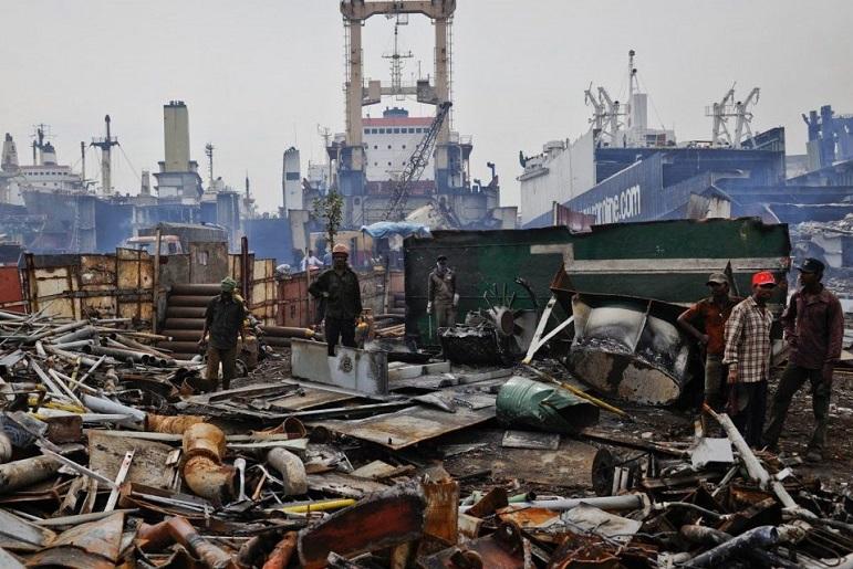 Operários no estaleiro de Alang, junto a estruturas secundárias, móveis, condutas e encanamentos.