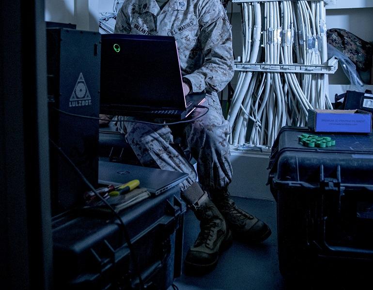 Staff Sgt. Brandon Ballantyne, chefe da secção de manutenção das comunicações do 11º Batalhão logistico de combate, da 11ª Unidade de Fuzileiros Expedicionária, trabalhando com uma impressora 3D a bordo do navio-doca anfíbio USS JOHN P. MURTHA (LPD-26). (imagem USMC, Adam Dublinske)