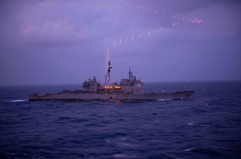 Rastos das munições tracejantes dum canhão Phalanx, iluminam a noite sobre o USS SAN JACINTO (imagem US Navy)