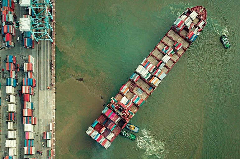 Um porta-contentores é assistido por dois rebocadores ao largar dum terminal portuário. (Imagem de Alexandre Gonçalves da Rocha por Pixabay)