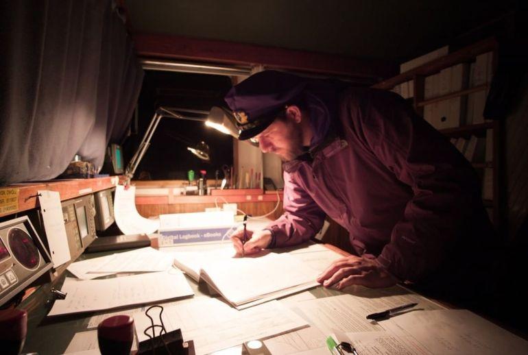Um oficial de quarto redige o diário náutico, um gesto de rotina que se repete à séculos (imagem Johannes Bargmann)