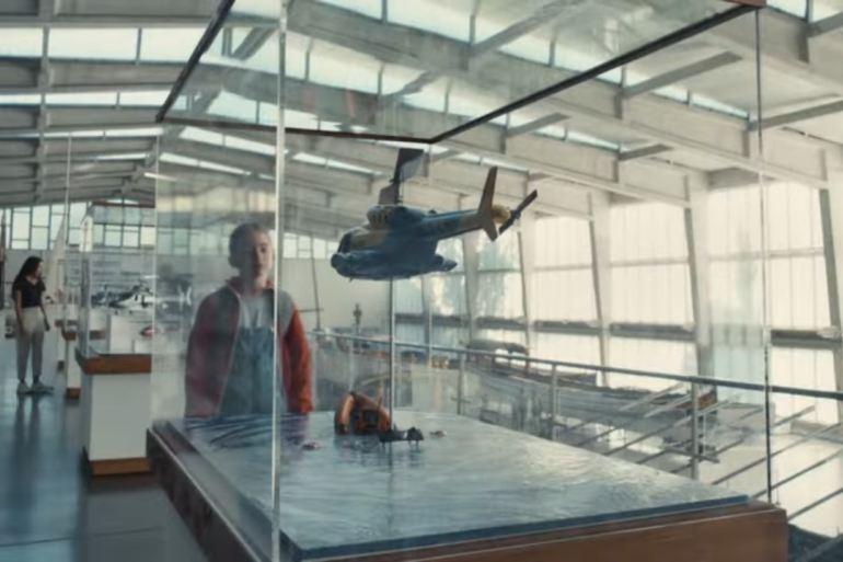 Uma criança observa um modelo dum helicóptero SAR no varandim do Pavilhão das Galeotas (fotograma do video da Apple)